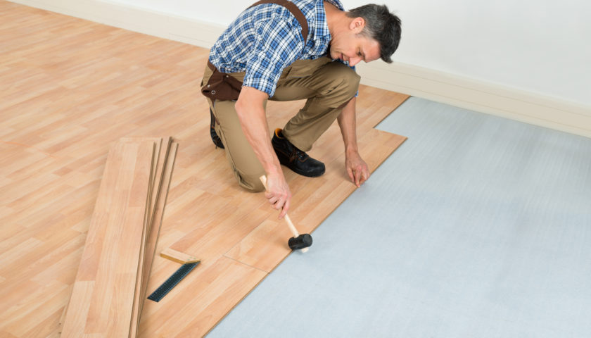 Man Installing New Laminated Wooden Floor